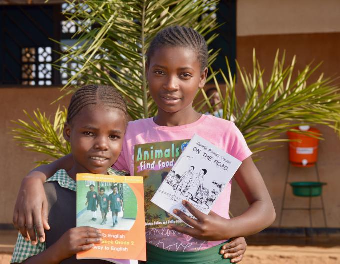 Chimuka (on the right) with her friend showing some of the books they received from Save the Children