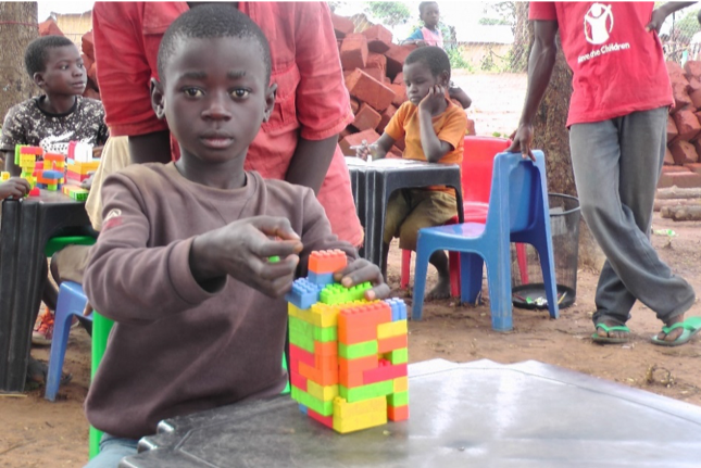 Moise making an elaborate design out of Lego - at the Save the Children CFS